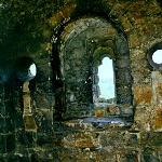 Interior of the Norman Chapel of St Nicholas at Richmond Castle, showing the arch windows and roundels.